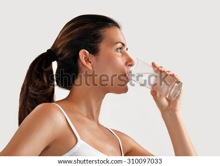 Young fitness sport woman drinking mineral water glass. - stock photo