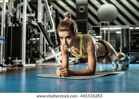 young fitness woman execute exercise plank in gym, horizontal photo - stock photo
