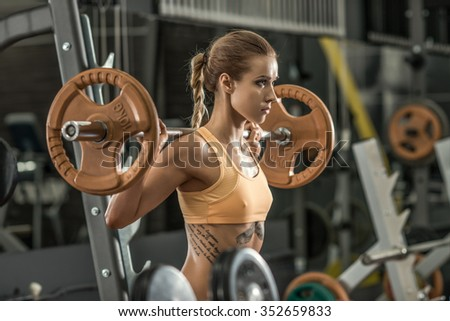 young fitness woman execute exercise with weight in gym, horizontal photo - stock photo