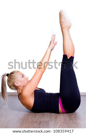 young fitness woman exercise abs lying on white floor - stock photo
