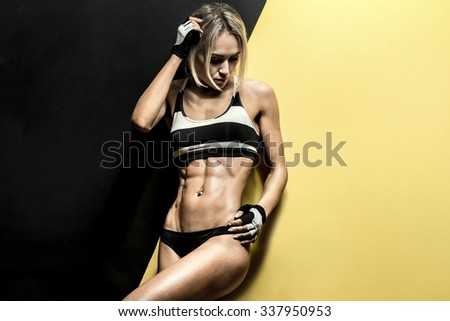 young fitness woman in swimsuit on black and yellow background, horizontal photo - stock photo