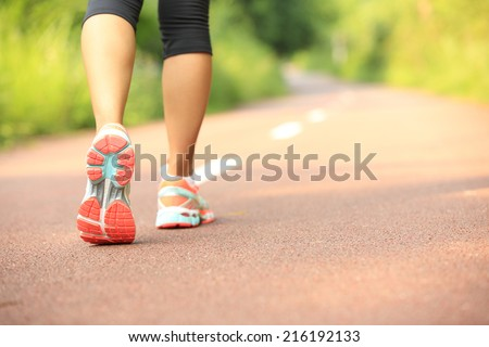young fitness woman legs running at forest trail  - stock photo