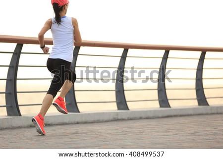 young fitness woman runner runnin on seaside bridge - stock photo
