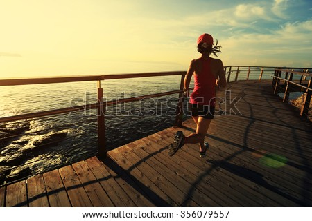young fitness woman runner running at seaside boardwalk - stock photo