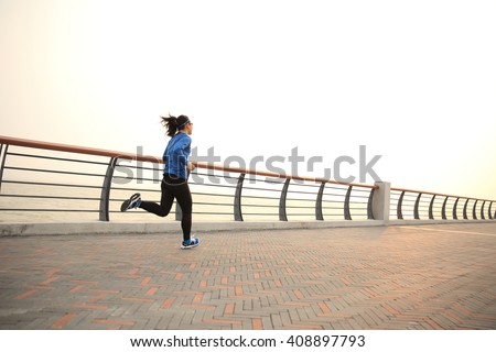 young fitness woman runner running on seaside bridge - stock photo