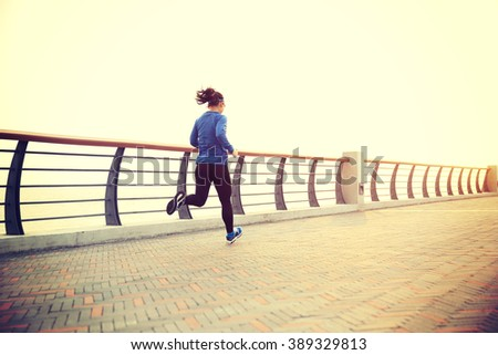 young fitness woman runner running on seaside road - stock photo