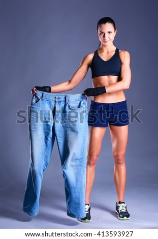 Young fitness woman showing that her old jeans  - stock photo