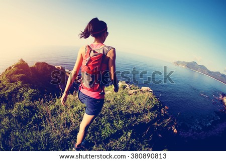 young fitness woman trail runner on sunrise seaside trail - stock photo