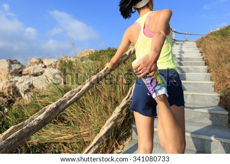 young fitness woman trail runner warm up on mountain stairs - stock photo