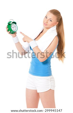 Young fitness woman with towel and green alarm clock, isolated on white background  - stock photo