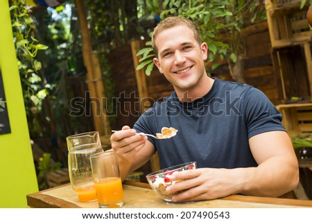 Young fitted man enjoying an organic juice and cereals in a raw restaurant - stock photo