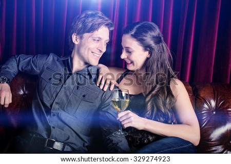 Young flirty couple with wine at a club lounge - stock photo