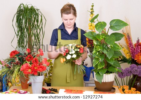 Young florist working on flower bouquet - stock photo