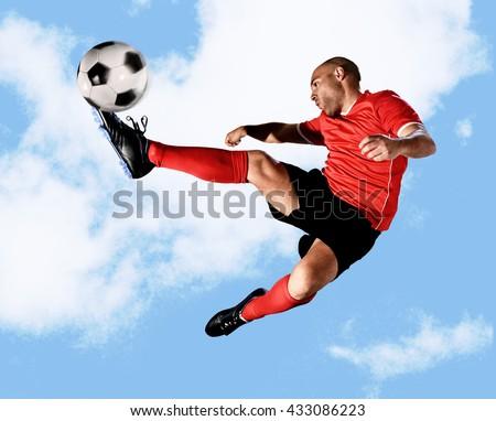 young football player kick ball in skillful volley jumping on the air in dynamic pose wearing red jersey and socks isolated on blue sky background shot in sport advertising style - stock photo