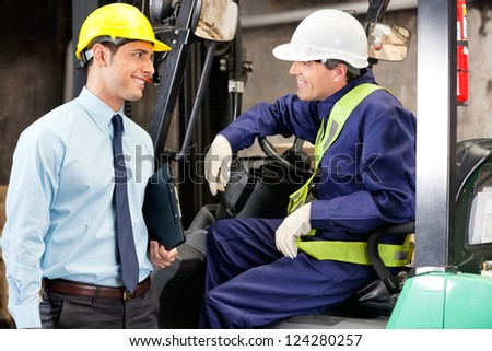 Young forklift driver communicating with supervisor at warehouse - stock photo