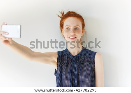 Young freckled Caucasian redhead woman in spotted dress making selfie using mobile phone, smiling at the camera, posing against white studio wall background. Technology concept - stock photo