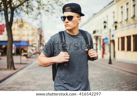 Young free beautiful fashionable hipster guy walking down the street, through the park, wearing a cap with a backpack, t-shirt, sunglasses, urban style, sport casual - stock photo
