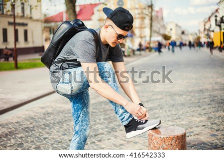 Young free beautiful hipster guy walking down the street, through the park, wearing a cap with a backpack t-shirt jeans leaning tying shoelaces on sneakers fashion sunglasses, Urban style Sport casual - stock photo
