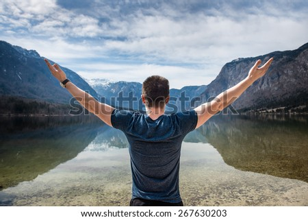 young freedom man hands up on a mountain lake - stock photo