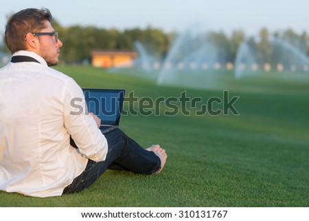 Young freelance businessman working outdoors on green meadow with laptop computer. Man in glasses sitting on the ground without shoes. - stock photo
