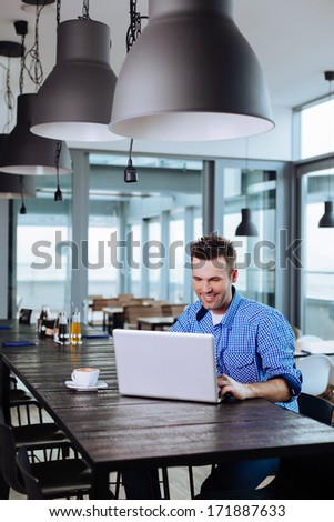 Young freelancer working on his laptop in a cafe - stock photo