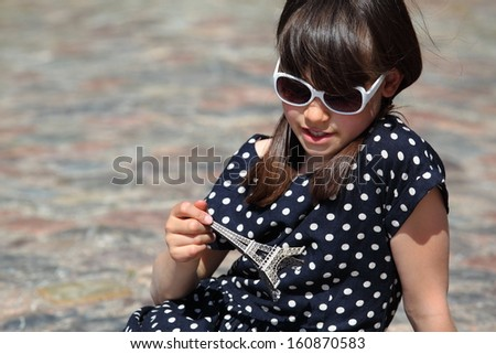 Young french girl in polka-dotted dress hold an Eiffel Tower miniature in her hand/Freckled French Girl - stock photo