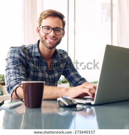 Young, fresh and vibrant young student smiling at the camera while working to become a businessman on his new notebook/laptop - stock photo