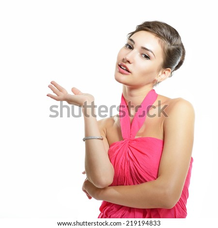 Young fresh attractive woman in pink dress pointing something with her hand, over white - stock photo