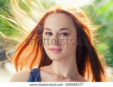 Young fresh redhead women looking at camera. Her hair fly with the wind. Backlit by sun. - stock photo
