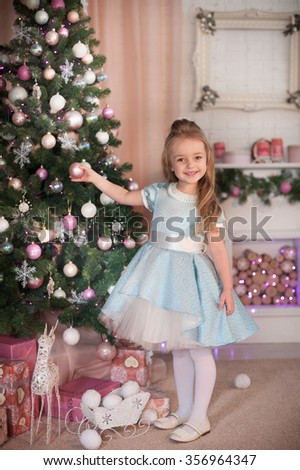 Young friendly girl smile and stay near gift box and dressed Christmas tree. New Year celebration. - stock photo