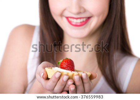 Young friendly smiling woman holding in her palm delicious strawberry tart cake in dough basket, studio, white background, close-up - stock photo