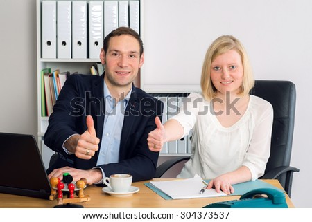 young friendly team in the office with thumbs up - stock photo