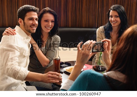 Young friends at the bar woman take picture of couple - stock photo