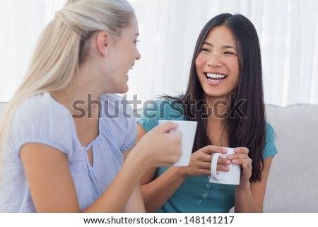 Young friends catching up over cups of coffee at home on couch - stock photo
