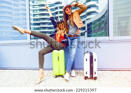 Young friends girls going crazy about their new trip, screaming laughing and having fun near airport with their bright luggage, enjoy travel together. Positive playful emotions, urban background. - stock photo