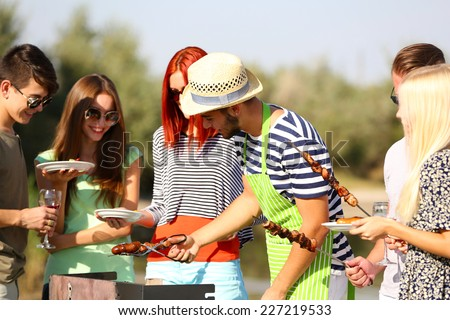 Young friends having barbecue party, outdoors - stock photo