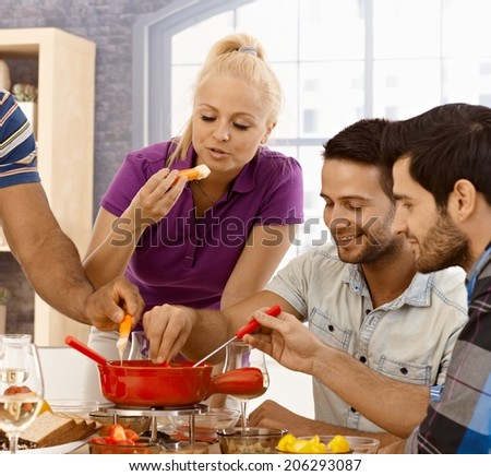 Young friends having cheese fondue at home. - stock photo