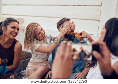 Young friends having fun at party being photographed with mobile phone. Young people sitting together enjoying party with one woman closing eyes of a man with another giving drink. - stock photo