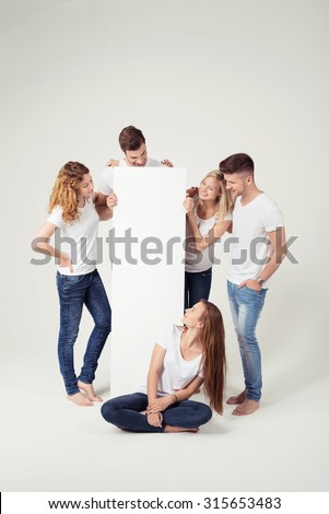 Young Friends in Casual Outfits Looking at the Empty Space of a White Board in a Vertical Position. Captured in Studio. - stock photo