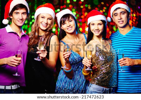 Young friends in Santa caps looking at camera while toasting at party - stock photo