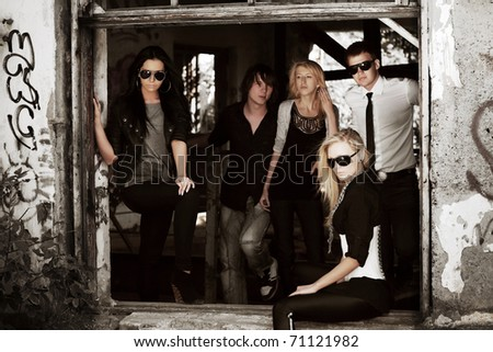 Young friends in the window of abandoned house - stock photo