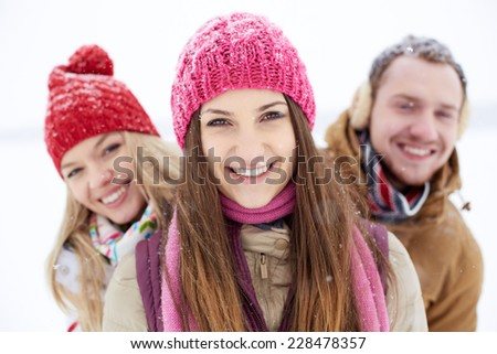 Young friends in winterwear looking at camera with pretty girl in front - stock photo