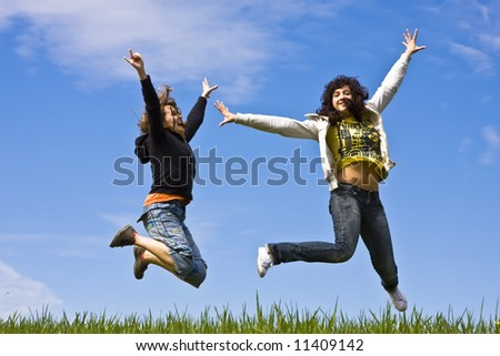 Young friends jumping on green meadow - stock photo