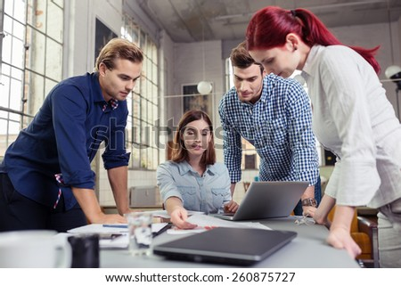 Young Friends Looking at the Reports on Top of Worktable Inside the Office. - stock photo