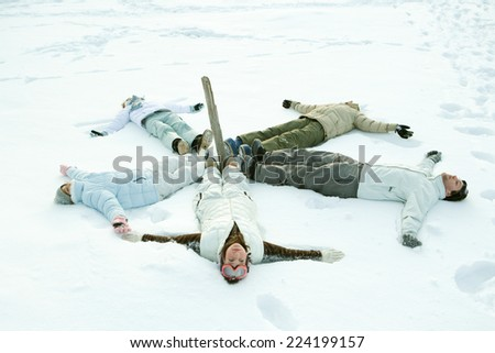 Young friends lying on ground in circle around wooden post - stock photo