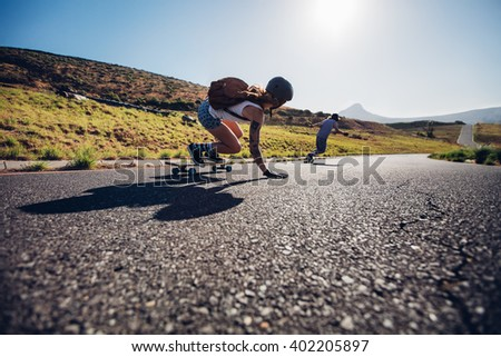 Young friends skating with their skateboards on rural road. Young people longboarding down the road on sunny day. - stock photo