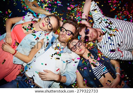 Young friends sleeping in confetti on the floor in nightclub after party - stock photo