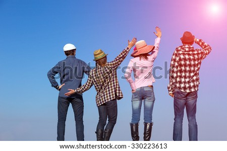 Young Friends Staying and Expressing Positive Emotions Four People Men and Women Together on Blue Sky Background Casual Jeans Style Dress Hands Gesturing Smiling Laughing Shining Sun - stock photo