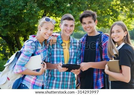 young  friends students with books  and gadgets on the background of  green park - stock photo