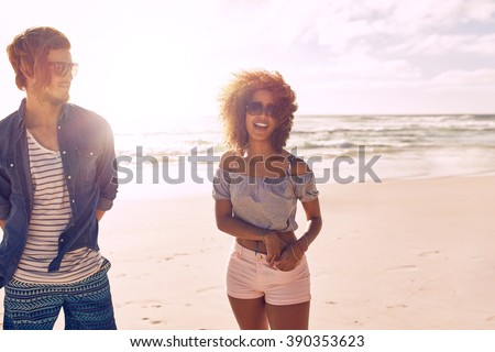 Young friends talking and laughing on a beach. Young woman smiling with her friend on a summer day at the sea shore. - stock photo